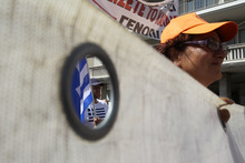 A protester with the Greek flag is seen through the banner held by a woman during a nationwide general strike in Athens, Wednesday, Sept. 26, 2012. About 50,000 people joined the union-organized march in central Athens on Wednesday, held during a general strike against new austerity measures planned in the crisis-hit country. (AP Photo/Thanassis Stavrakis)