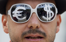 A protester wears glasses with the euro and dollar symbols painted on the lenses before a protest march in Madrid, Tuesday Sept. 25, 2012.  Thousands of people are expected to converge on the Spanish Parliament to protest the conservative government's handling of the economic crisis and to demand fresh elections. Organizers of the 'Occupy Congress' protest hope to form a protest chain around the building but heavy police reinforcements are likely to keep them well away. (AP Photo/Paul White)