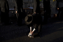 An ultra-Orthodox Jewish man holds a chicken during the Kaparot ritual, in which it is believed that one transfers one's sins from the past year into the chicken, in the Ultra-Orthodox city of Bnei Brak near Tel Aviv, Israel, Tuesday, Sept. 25, 2012. The ritual is performed before the Day of Atonement, Yom Kippur, the holiest day in the Jewish year which starts at sundown Tuesday. (AP Photo/Oded Balilty)