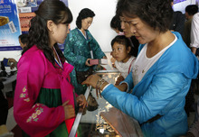 A North Korean woman looks at gold watches at a North Korean booth at a trade fair at the Three Revolution Exhibition Hall in Pyongyang Tuesday, Sept. 25, 2012. (AP Photo/Vincent Yu)