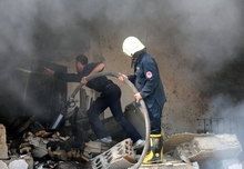 This photo released by the Syrian official news agency SANA shows Syrian firefighters extinguishing a fire in a damaged school after a bomb attack in Damascus, Syria, Tuesday, Sept. 25, 2012. Several bombs went off Tuesday inside a school in the Syrian capital that activists say was being used by regime forces as a security headquarters. Ambulances rushed to the area and an initial report on state media said several people were wounded. (AP Photo/SANA)