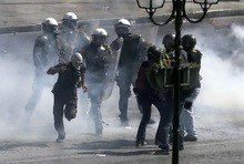 Riot police officers try to arrest a masked demonstrator during clashes in Athens, Wednesday Sept. 26, 2012. Police clashed with protesters hurling petrol bombs and bottles after an anti-government rally called as part of a general strike in Greece turned violent. About 50,000 people joined the union-organized march held during a general strike against new austerity measures planned in the crisis-hit country. (AP Photo/Dimitri Messinis)