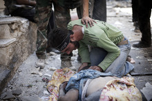 A Free Syrian Army fighter weeps over the body of a comrade killed by a tank blast in Aleppo, Syria, Wednesday, Sept. 26, 2012. Syria's unrest began in March 2011 when protests calling for political change met a violent government crackdown. Many in the opposition have since taken up arms as the conflict morphed into a civil war that activists say has killed nearly 30,000 people. Over the past few months, the rebels have increasingly targeted security sites and symbols of regime power in a bid to turn the tide in the fighting.(AP Photo/Manu Brabo)