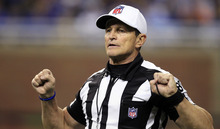 FILE - In this Dec. 24, 2011, file photo, referee Ed Hochuli (85) signals during the second quarter of an NFL football game between the Detroit Lions and the San Diego Chargers in Detroit. The NFL and referees' union reached a tentative agreement on Wednesday, Sept. 26, 2012, to end a three-month lockout that triggered a wave of frustration and anger over replacement officials and threatened to disrupt the rest of the season. (AP Photo/Carlos Osorio, File)