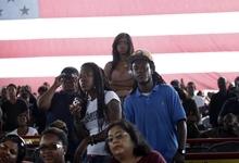 People stand to get a glimpse of President Barack Obama as he speaks at the Farm Bureau Live at Virginia Beach, Va., on Thursday, Sept. 27, 2012. (AP Photo/The Virginian-Pilot, Preston Gannaway)