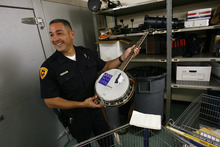Francisco Kjolseth  |  The Salt Lake Tribune Detective Mike Hamideh with the Salt Lake City Police department smiles over a banjo initially kept for safe keeping with a sticker that reads