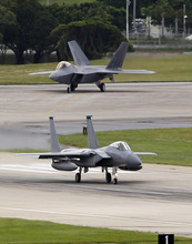 In this Aug. 14, 2012 file photo, a U.S. Air Force F-22 Raptor, top, waits as an F-15 Eagle begins its take off run at Kadena Air Base on the southern island of Okinawa, in Japan. Years before F-22 pilots began getting dizzy in the cockpit, before one struggled to breathe as he tried to pull out of a fatal crash, before two more went on television to say the plane was so unsafe they refused to fly it, a small circle of U.S. Air Force experts knew something was wrong with the prized stealth fighter jet.  (AP Photo/Greg Baker, File)