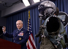 FILE - In this July 31, 2012 file photo, Air Combat Command's director of operations Maj. Gen. Charlie Lyon, left, holds a valve during a news conference at the Pentagon in Washington to provide an update on the Air Force Scientific Advisory Board study into life support systems installed on the F-22 and operations. The U.S. is hoping a dozen F-22 stealth fighters now roaring through the skies of southern Japan will prove its most prized combat aircraft is finally ready to resume full operations after years of investigations into why its pilots were getting dizzy and disoriented. But questions remain over whether the Air Force has taken enough action to fix a potentially bigger problem - the shriveling of programs to test cockpit life support systems after nearly 20 years of budget cuts, downsizing and outsourcing. (AP Photo/Manuel Balce Ceneta, File)