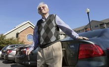 Benjamin Benson poses in the parking lot outside his residence at a senior community in Peabody, Mass. A large study from Canada found that when doctors warn patients, and driving authorities, that they may be medically unfit to be on the road, there's a drop in serious crash injuries among those drivers.  (AP Photo/Charles Krupa)