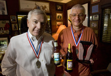 Steve Griffin  |  The Salt Lake Tribune   Wasatch Beers managing partner Greg Schirf and Squatters founder Peter Cole with first place medals and top prize trophy for Mid-Size Brewing Company and Mid-Size Brewing Company Brewer of the Year at the Great American Beer Festival in September 2010.Utah Brewers Cooperative also won gold medals for Summerbrau and Squatter's Wit as well as a bronze for Hell's Keep.