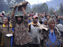 Enga clan members in Papua New Guinea offer pieces of pork in a 2011 village court compensation ceremony to settle a homicide case without starting a war among clans. The ceremony took place near the Enga provincial capital of Wabag. Courtesy Polly Wiessner  |  University of Utah.