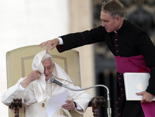 Monsignor Georg Gaenswein, right, helps Pope Benedict XVI pull back his mantle blown by the wind as he reads his message during the weekly general audience at the Vatican, Wednesday, Sept. 26, 2012. (AP Photo/Gregorio Borgia)