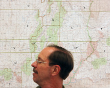 Steve Griffin | The Salt Lake Tribune   Grand County Search and Rescue commander, Jim Webster, stands in front of a map of Utah at the search and rescue offices in Moab, Utah Thursday September 13, 2012. Grand and Wayne counties are charging people for search and rescues. One man received a $1,500 bill for being rescued after his raft overturned on the Colorado River. A North Carolina man received a $4,000 bill after he rescued from Bluejohn Canyon.