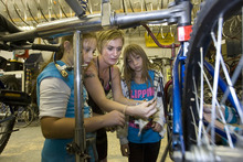 Paul Fraughton | Salt Lake Tribune Hailey Broussard,center, shows Cianne Paul, left, and Angel Martinez  how to remove the lower bracket on a bicycle.   Thursday, September 27, 2012
