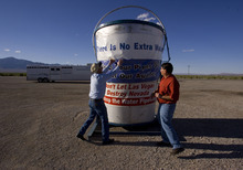 File  |  The Salt Lake Tribune  Rancher Dean Baker, left, and Snake Valley resident Gary Perea fix a banner on a bucket protesting a plan to pump water from the valley's aquifer.