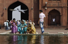 Indian Muslim women wash themselves near a fountain as a pigeon flies by at the Jama Masjid, or the Grand Mosque, in New Delhi, India, Friday, Sept. 28, 2012. The Jama Masjid is one of India's biggest mosques. (AP Photo/Altaf Qadri)