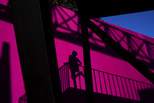 A woman poses for a photo, casting her shadow on an empty advertisement board nearby at the 798 Art District in Beijing Friday, Sept. 28, 2012. (AP Photo/Alexander F. Yuan)