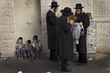 Ultra-Orthodox Jewish men check etrogs, a lemon-like citrus fruit, for blemishes to determine if they are ritually acceptable, before buying it as one of the four items used as a symbol on the Jewish holiday of Sukkot, in Jerusalem's Mea Shearim neighborhood, Thursday, Sept. 27, 2012. According to the Bible, during the Sukkot holiday, known as the Feast of the Tabernacles, Jews are commanded to bind together a palm frond, or
