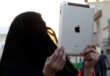 A Bahraini woman uses an iPad to photograph a rally in Diraz, Bahrain, on Thursday, Sept. 27, 2012, against a film made in the United States that denigrates Islam's founding Prophet Muhammad. A few hundred people participated in the march, chanting slogans against the United States and Israel. (AP Photo/Hasan Jamali)