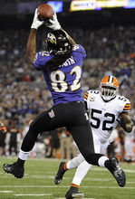 Baltimore Ravens wide receiver Torrey Smith (82) pulls in a touchdown pass under pressure from Cleveland Browns middle linebacker D'Qwell Jackson (52) during the first half of an NFL football game in Baltimore, Thursday, Sept. 27, 2012. (AP Photo/Nick Wass)