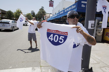Adam Kessel, right, and Glen Greenberg, both of Calabasas, Calif., sell T-shirts near Interstate 405 in Los Angeles, Friday, July 15, 2011. The City of Angels is on edge as the hours tick off until