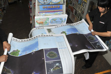 In this Sept. 19, 2012 photo, employees of a state-owned book store roll up newly-published maps of disputed islands, called Diaoyu in China and Senkaku in Japan, at a state-run book store in Beijing.  China hastily published the map to help maintain public outrage over the Japanese government's purchase of some of the islands from their private Japanese owners. Beijing also has engaged in another type of mapmaking that may end up escalating the conflict. (AP Photo)  CHINA OUT