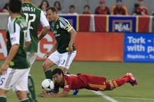 Real Salt Lake's Javier Morales falls as he battles for control of the ball with Portland Timbers' Jack Jewsbury (13) in the first half of an MLS soccer game Saturday, Sept. 22, 2012, in Sandy, Utah. (AP Photo/Rick Bowmer)