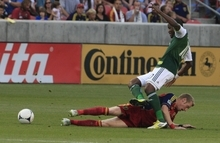 Real Salt Lake's Nat Borchers slides as he tackles Portland Timbers' Danny Mwanga (10) in the first half of an MLS soccer game Saturday, Sept. 22, 2012, in Sandy, Utah.  (AP Photo/Rick Bowmer)