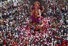 Devotees crowd around an idol of elephant-headed Hindu God Ganesha being carried for immersion in the Arabian Sea on the final day of the ten-day long Ganesh Chaturthi festival in Mumbai, India, Saturday, Sept. 29, 2012. (AP Photo/Rajanish Kakade)