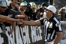 FILE - In this Oct. 31, 2010, file photo, referee Ed Hochuli (85) greets Oakland Raiders fans before an NFL football game against the Seattle Seahawks in Oakland, Calif. The NFL and referees' union reached a tentative agreement on Wednesday, Sept. 26, 2012, to end a three-month lockout that triggered a wave of frustration and anger over replacement officials and threatened to disrupt the rest of the season. (AP Photo/Paul Sakuma, File)