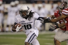 Utah State wide receiver Chuck Jacobs (10) pulls away from UNLV defensive backs Peni Vea (42) and Tajh Hasson (29) on his way to a touchdown in the second quarter of an NCAA college football game Saturday, Sept. 29, 2012, in Logan, Utah.  (AP Photo/Rick Bowmer)