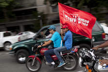 A supporter of Venezuela's President Hugo Chavez holds a flag that reads in Spanish: