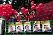 Supporters of Venezuela's President Hugo Chavez stand in a trailer bed as they take part in a campaign caravan through Caracas, Venezuela, Friday, Sept. 28, 2012. Venezuela's presidential election is scheduled for Oct. 7. (AP Photo/Rodrigo Abd)