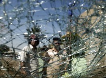 Iraqis are seen through a shattered windshield of a vehilce at the scene of a car bomb attack in Baghdad, Iraq, Sunday, Sept 30, 2012. A rapid-fire series of explosions in Baghdad while Iraqis were going to work on Sunday morning, killed and wounded scores of people, police said. (AP Photo/Karim Kadim)