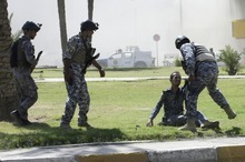 Iraqi policemen help an injured colleague after a car bomb attack near the Sacred Heart Church in the Karrada Neighborhood of Baghdad, Iraq, Sunday, Sept. 30, 2012. A rapid-fire series of explosions in Baghdad while Iraqis were going to work on Sunday morning, killed and wounded scores of people, police said. (AP Photo/Khalid Mohammed)