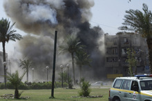 Plumes of smoke rise from the scene of a car bomb attack near the Sacred Heart Church in the Karrada Neighborhood of Baghdad, Iraq, Sunday, Sep. 30, 2012. A rapid-fire series of explosions in Baghdad while Iraqis were going to work on Sunday morning, killed and wounded scores of people, police said. (AP Photo/Khalid Mohammed)
