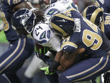 Seattle Seahawks running back Marshawn Lynch (24) is tackled by St. Louis Rams defensive end Robert Quinn during the first half of an NFL football game Sunday, Sept. 30, 2012, in St. Louis. (AP Photo/Tom Gannam)