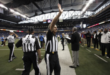 Line judge Ron Marinucci gives a waves to cheering fans while walking on the field before the Minnesota Vikings-Detroit Lions NFL football game in Detroit Sunday, Sept. 30, 2012.  (AP Photo/Paul Sancya)