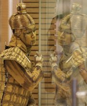A Filipino performer dressed as China's terracotta warrior gestures to a saleslady at a mall in Manila's Chinatown, Philippines on Sunday Sept. 30, 2012. The mall held several events as part of its celebrations for the Chinese mid-autumn festival. (AP Photo/Aaron Favila)