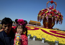 A child bites a bottle as she poses for photograph with her father near a giant flower pot on display at Tiananmen Square in Beijing Sunday, Sept. 30, 2012. Hundreds of thousands foreign and domestic tourists are expected to flock to the square to celebrate the Mid-Autumn Festival and 63rd National Day over the week-long holidays starting on Sept. 30. (AP Photo/Andy Wong)