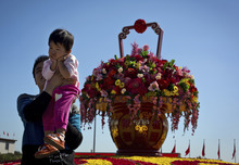 A child reacts as she is lifted up to pose near a giant flower pot on display at Tiananmen Square in Beijing Sunday, Sept. 30, 2012. Hundreds of thousands foreign and domestic tourists are expected to flock to the square to celebrate the Mid-Autumn Festival and 63rd National Day over the week-long holidays starting on Sept. 30. (AP Photo/Andy Wong)