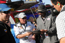Former Philadelphia Eagle Brian Dawkins, center right, grand marshal for the race, signs autographs while walking through the garage prior to the NASCAR Sprint Cup Series auto race Sunday, Sept. 30, 2012, at Dover International Speedway in Dover, Del. (AP Photo/The News-Journal, ) NO SALES