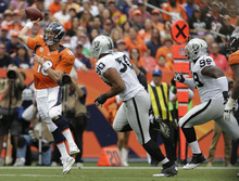 Denver Broncos quarterback Peyton Manning (18) throws on the run during the first quarter of an NFL football game against the Oakland Raiders, Sunday, Sept. 30, 2012, in Denver. (AP Photo/Joe Mahoney)