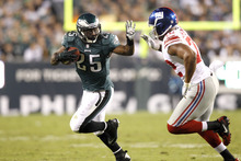 Philadelphia Eagles running back LeSean McCoy (25) runs with the ball as New York Giants defensive end Osi Umenyiora (72) defends on the play during the first half of an NFL football game Sunday, Sept. 30, 2012, in Philadelphia. (AP Photo/Mel Evans)