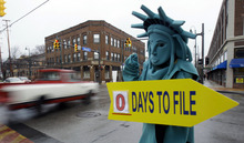 FILE-In this Monday, April 18, 2011, file photo, Max Martinez, dressed as the Statue of Liberty, tries to alert motorists on the final day to file taxes. A typical middle-income family making $40,000 to $64,000 a year could see its taxes go up by $2,000 in 2013 if lawmakers fail to renew a lengthy roster of tax cuts set to expire at the end of 2012, according to a new report Monday, Oct. 1, 2012. Taxpayers across the income spectrum would be hit with large tax hikes, the Tax Policy Center said in its study, with households in the top 1 percent income range seeing an average tax increase of more than $120,000, while a family making between $110,000 to $140,000 could see a tax hike in the $6,000 range. (AP Photo/Tony Dejak)