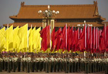 Chinese soldiers holding red and yellow flags stand at Tiananmen Square during a ceremony marking National Day in Beijing on Monday, Oct. 1, 2012.  (AP Photo/Andy Wong)