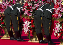 Chinese Paramilitary policemen prepare to carry the wreaths of flowers to the Monument to the People's Heroes during a ceremony marking National Day at Tiananmen Square in Beijing Monday, Oct. 1, 2012.  (AP Photo/Andy Wong)