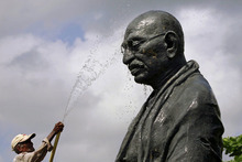 A worker sprays water on a statue of the late Mahatma Gandhi on the eve of his birth anniversary at Gandhi Park in Bhubaneswar, eastern India, Monday, Oct. 1, 2012. Gandhi, known as the