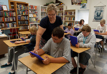 Trent Nelson  |  The Salt Lake Tribune Dixon Middle School teacher Leann Moody helps Jacen Hansen with an iPad during a reading class in Provo, Utah, Tuesday September 25, 2012.