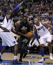 Utah Jazz's Al Jefferson (25) drives to the basket through Dallas Mavericks' Brendan Haywood, left, and Shawn Marion (0) in the second half of an NBA basketball game on Friday, Jan. 27, 2012, in Dallas. Jefferson contributed 19-points in the 116-101 loss to the Mavericks. (AP Photo/Tony Gutierrez)